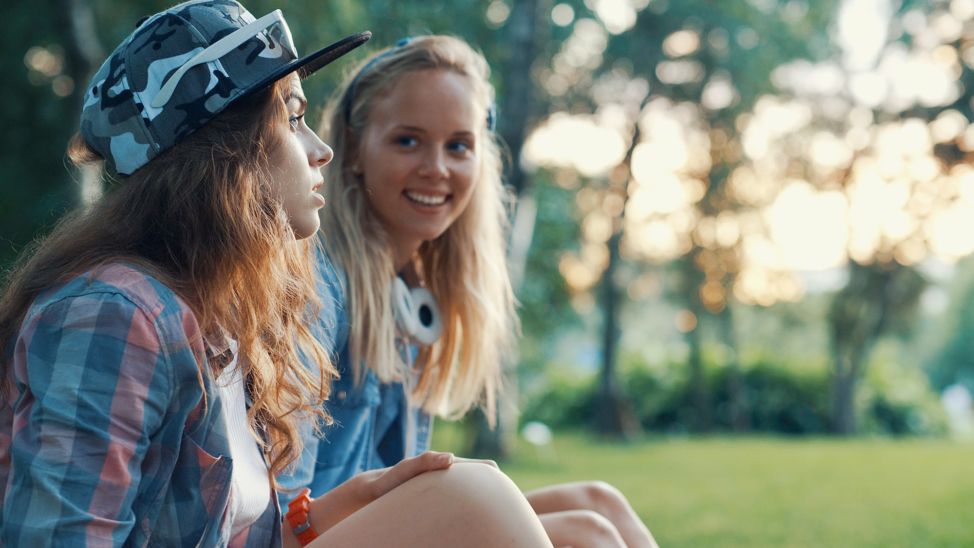 Young teen smiles at her friend as they sit in a grassy field. She is feeling more open with others after going to group therapy for teen girls in west bloomfield, mi. Therapyology offers adolescent therapy in west bloomfield, mi, therapy for girls in west bloomfield, mi, and more. contact us to start therapy for teens in west bloomfield, mi.