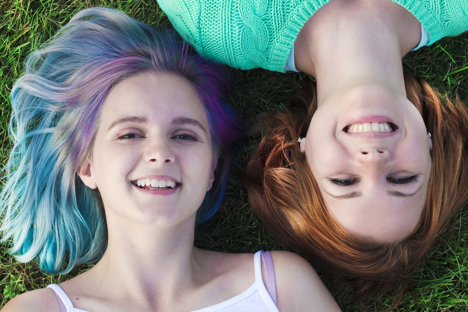 Two young teen girls lay in the grass as they smile at the camera above them. They are happy that they've found the Rainbow Group with Therapyology. We offer support for lgbtq youth in west bloomfield, mi, lgbt youth groups in west bloomfield, mi, and more.