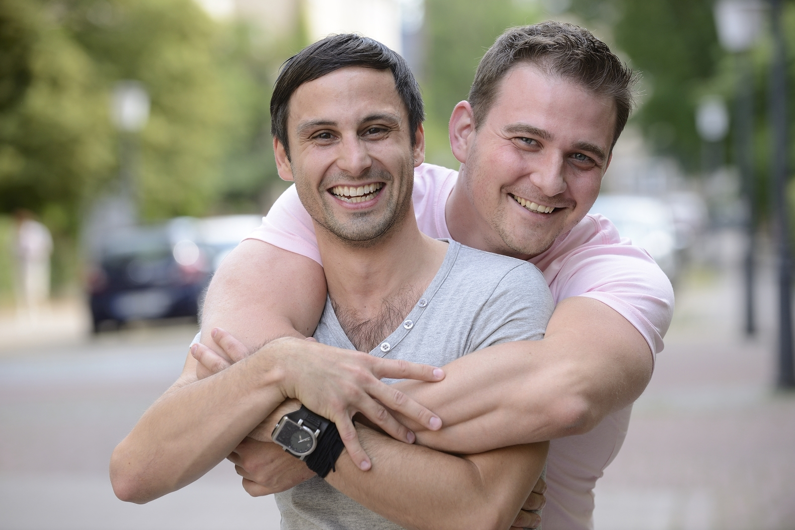 A gay couple stand outdoors as they look at the camera. A man is embracing his partner from behind, and both are smiling brightly. They are feeling good after meeting a lgbt ally in west bloomfield, mi at Therapyology. We offer lgbtq therapy in west bloomfield, mi, lgbt affirmative therapy in west bloomfield, mi, gender therapy in west bloomfield, mi, and more.