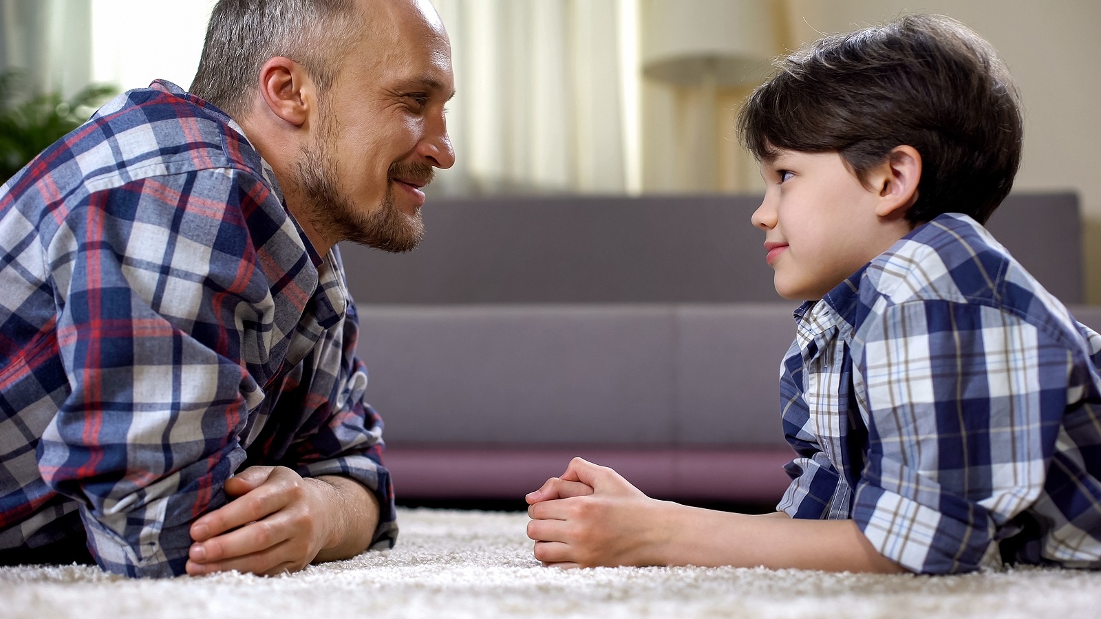 Man smiles at son as both lay on the carpet in front of one another. They are happy that they've found divorce therapy for children in West Bloomfield, MI.  Therapyology offers therapy for teens of divorce, child divorce therapy, and more. Contact us for child therapy for divorce today.