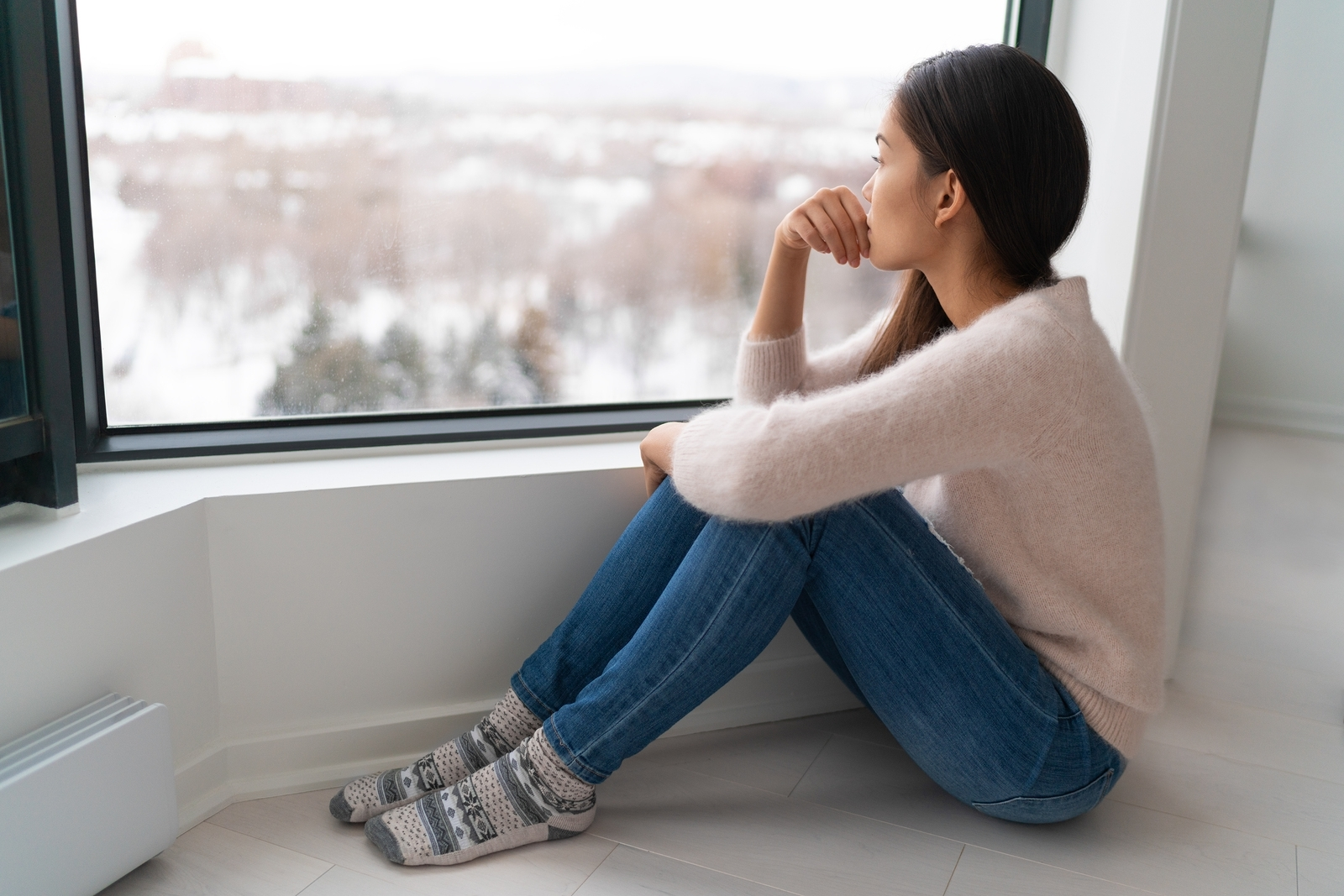 Young woman appears depressed as she sits on the floor looking out the window. She is thinking about past trauma. Therapyology offers trauma therapy in West Bloomfield, MI. Contact us for trauma counseling, trauma informed therapy, and more. Contact us to get in touch with a trauma therapist online in michigan.