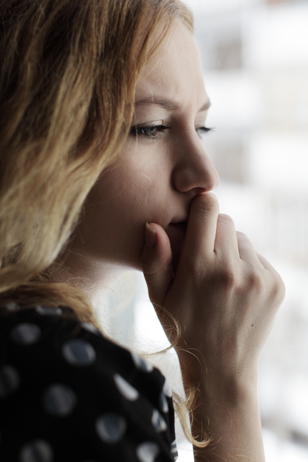 A close up of a woman holding her hand against her mouth while looking out a window. She appears worried about something as she is deep in thought. This could symbolize the fear and apprehension of a young adult. We offer transitions counseling in West Bloomfield, MI for young adults adapting to change. Contact a young adult therapist for young adult therapy and other services.