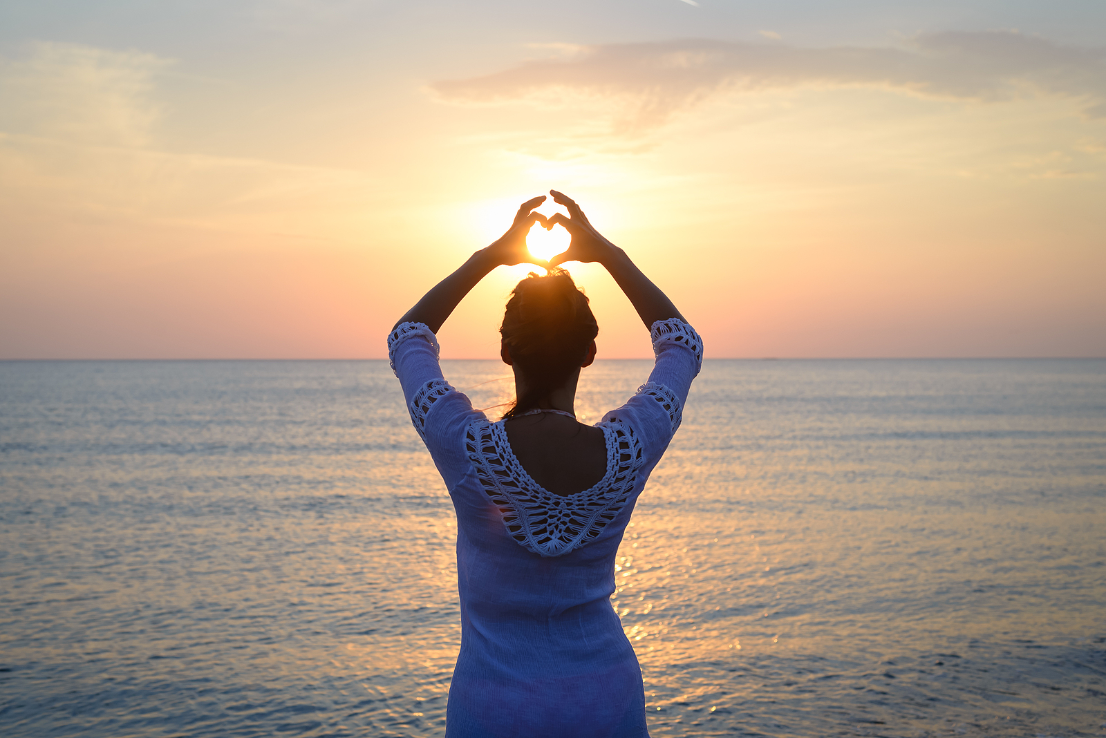 Woman at the beach holds her hands above her head in a heart shape. Shining between her hands, the sun can be seen setting over the water. This symbolizes the peace people feel after dealing with grief. We offer grief counseling in West Bloomfield, MI. If you're going through the stages of grief, contact a grief counselor for support!