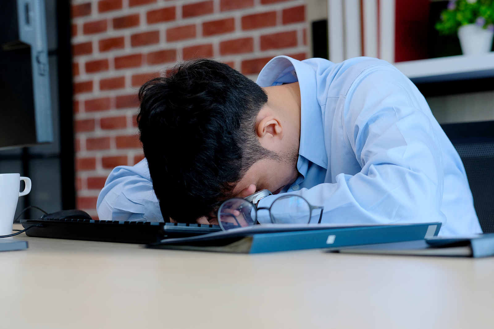 A man hides his face by laying his head on his desk. This could symbolize the stress of starting a first job. We offer support for young adults adapting to change. Contact us for transitions counseling in West Bloomfield, MI, life transition counseling, and more.