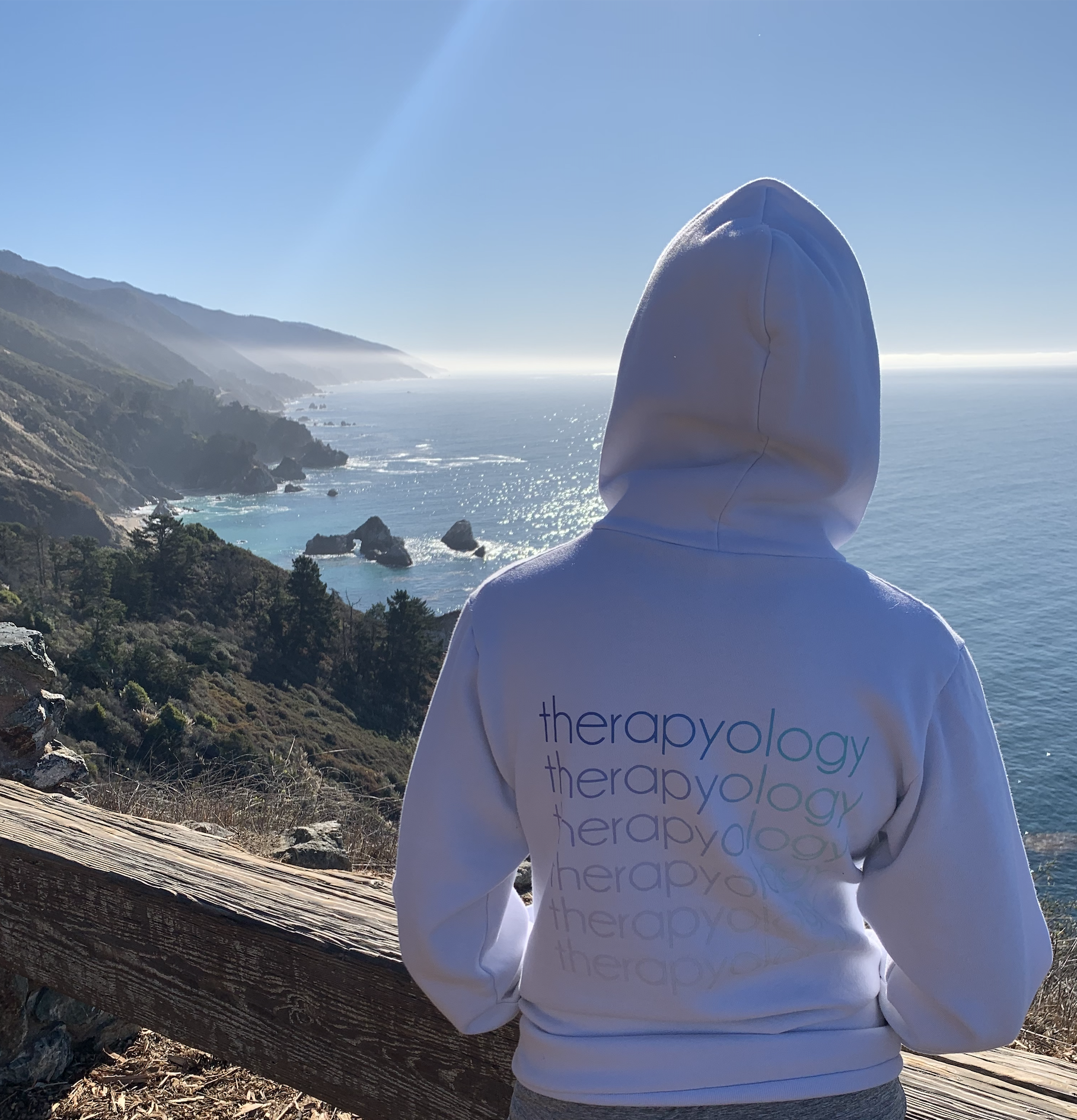 """A person wearing a hoodie with the text """"therapyology"""" repeated on the back looks out over the coast. Camp Therapyology is a mental health summer camp for teens in Michigan. We also offer summer camps for teens in California. Search """"summer camps 2021 near me"""" to learn more info!"""