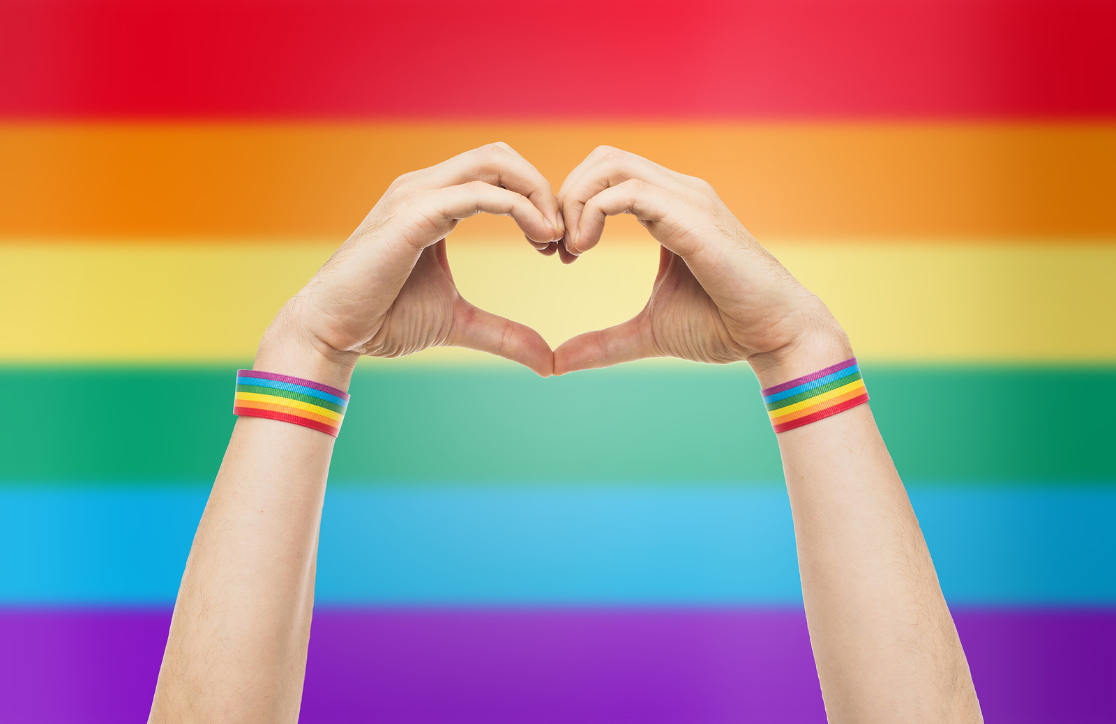A pair of hands make a heart symbol with LGBTQ colors behind. Group therapy in West Bloomfield, MI can offer support. Learn about our LGBTQ youth groups in West Bloomfield, MI and the other services we offer including trauma therapy groups in West Bloomfield, MI.