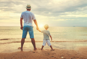 a father stands with his son looking at the ocean sunset. This represents the support group therapy in West Bloomfield, MI can provide. Contact a teenage support group for teen group therapy in West Bloomfield, MI or group therapy in San Fransisco, CA